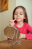 Applying lipstick. Little girl doing makeup in front of small mirror Royalty Free Stock Image
