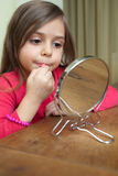Applying lipstick. Little girl making makeup in front of small mirror Stock Photos