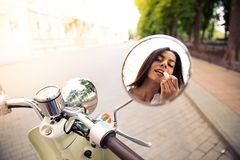 Applying lipstick in mirror motocycle Stock Image