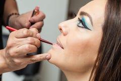 Applying lipstick to a white woman Royalty Free Stock Photos