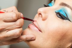 Applying lipstick to a white woman Stock Images