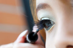 Applying liquid eyeliner with brush, close up Stock Images