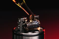 Applying liquid with nicotine in the coils on the RDA. Over the dark background Royalty Free Stock Image