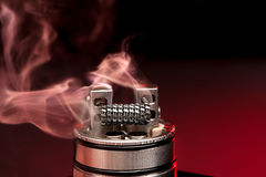 Applying liquid with nicotine in the coils on the RDA. Over the dark background Stock Image