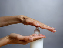 Applying liquid soap. Woman applying liquid soap on her hands stock image