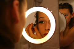 Applying Make-up. Woman applying make-up in bathroom mirror Royalty Free Stock Photography