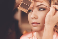 Applying make up on blond woman Royalty Free Stock Photography