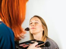 Applying make up, two women. Royalty Free Stock Photography