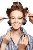 Applying make-up. Young woman in curler in her hair and one eye with make-up,she is expressing her emotions Stock Image