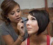 Applying Makeup. Horizontal image of young girls applying eye makeup stock image