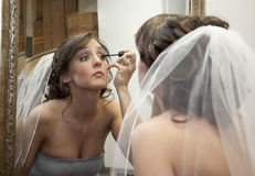 Applying Makeup. Horizontal image of a young bride applying makeup prior to her wedding royalty free stock images