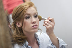 Applying Makeup. Horizontal image of a young woman applying makeup in a mirrow royalty free stock photo