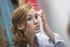 Applying Makeup. Horizontal image of a young woman applying makeup in a mirror royalty free stock image