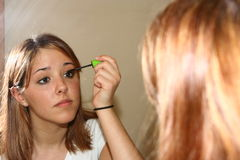 Applying makeup. Young woman putting on make up in the mirror Stock Photos