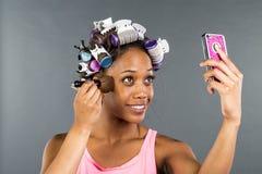 Applying Makeup di modello nero Immagine Stock