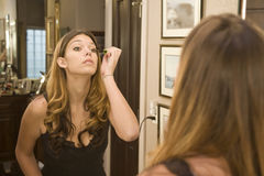Applying makeup in the mirror Royalty Free Stock Images