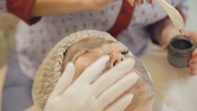 Applying marine mug mask on female face. Full HD stock footage