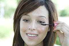 Applying mascara. A young woman smiles as she brushes on some mascara Royalty Free Stock Images