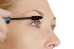 Applying mascara. Close up of lady applying eye mascara stock photo
