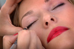 Applying mascara to lady Royalty Free Stock Image