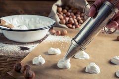 Applying meringues on baking paper for macaroons Stock Image