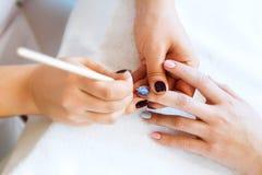Applying nail polish on nails Stock Images