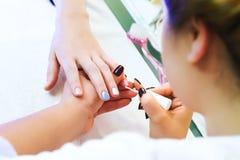 Applying nail polish on nails Stock Image