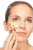 Applying natural cosmetics. Young beautiful woman applying natural cosmetics depicting concept with nuts in cram stock photography