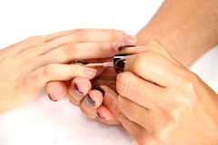 Applying natural nail polish on fingers Stock Photos