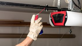 Applying oil to a chain of a garage door opener. Preventive maintenance on a garage door opener chain with some oil stock images