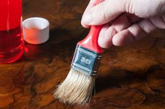 Oiling a wood table with a brush. Applying oil on a wood table with a brush Royalty Free Stock Photos