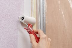Applying paint roller to the wall in the household. Renovation in home conditions. Light background royalty free stock photos