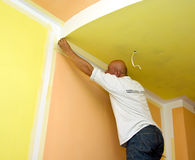 Applying paint tape. A man painting a room in yellow and orange, applying a painting tape protecting the corner where the paint is white Stock Images