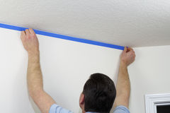 Applying Painter's Tape. Man preparing to paint ceiling by masking off the wall beneath it with blue painter's tape stock photos