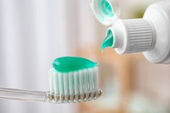 Applying paste on toothbrush. Against blurred background, closeup stock photography