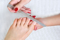 Applying pedicure, using nail file Royalty Free Stock Images