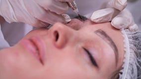 Applying pigment machine on the eyebrow. Permanent makeup. 4K Slow Mo. Applying pigment machine on the eyebrow. Permanent makeup stock video footage