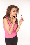 Applying pink lipgloss royalty free stock image