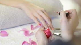 Applying pink nail polish. Closeup shot of a beautician applying nail polish to female nail in a nail salon. Close up of a woman hand with pink nailpolish after stock video