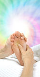 Applying pressure to Solar Plexus Zone. Reflexologist working on Solar Plexus area of foot with soft spiral of rainbow colors in background Royalty Free Stock Photos