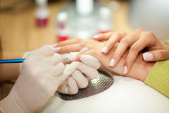 Applying professional french manicure at beauty treatment Royalty Free Stock Images
