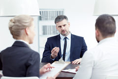 Applying for promotion. Man applying for promotion during interview with board members stock image