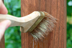 Applying protective varnish/paint to a wooden fence Royalty Free Stock Photography
