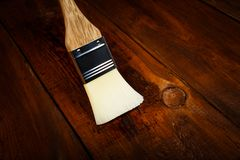 Applying protective varnish on a wooden table Royalty Free Stock Images