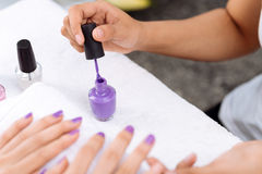 Applying purple nail polish Royalty Free Stock Image