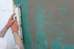 Applying putty to the  wall using a spatula Royalty Free Stock Image