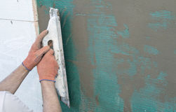 Applying putty to the  wall using a spatula Stock Photos