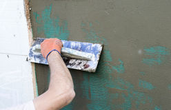 Applying putty to the  wall using a spatula Royalty Free Stock Images