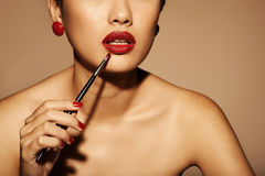 Applying red lipstick Stock Photo