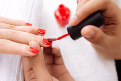 Applying  red nail polish Stock Photography